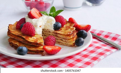 Stack of keto pancakes made of coconut flour or almond flour, served with berries and whipped cream on plate. One slice eaten already.