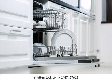 Stack of kitchenware in open dishwashing machine