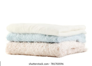 Stack of knitted sweaters on white background