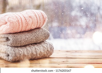 Stack of knitted sweaters on wooden tableon winter nature background.