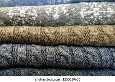 stack of knitted sweaters with snowflakes. Winter photo background. Knitted wool sweaters. Pile of knitted winter clothes, sweaters, knitwear.