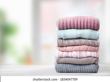 Stack of knitted textured clothing on table empty space.Colorful winter clothes,warm apparel.Heap of knitwear.Autumn garment. - Shutterstock ID 1834047709