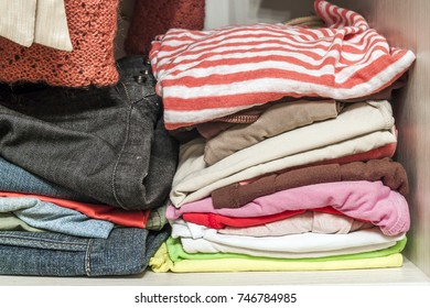 A stack of knitted warm woolen clothes in wardrobe close up
