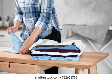 Stack of laundry and woman folding clothes on table indoors