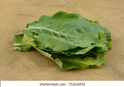 Stack of leaves of raw collard greens on burlap