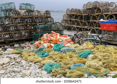 A stack of lobster traps and fishing equipment on the shore of the ocean near the fishing village