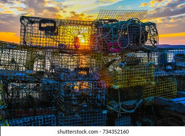 A stack of lobster traps and fishing equipment on a dock on Passamaquoddy Bay in Lubec, Maine, as the sun sets in the background