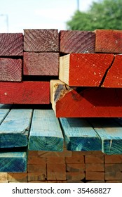 A stack of lumber of varying shapes, sizes and colors, delivered to a construction site