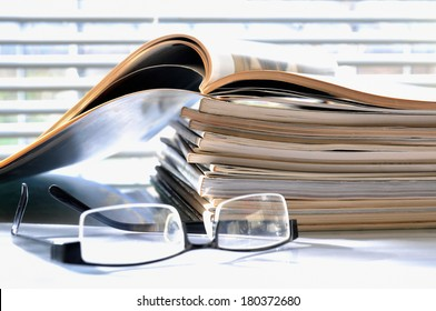 Stack of magazines with black glasses