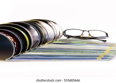 Stack of magazines with glasses on top.