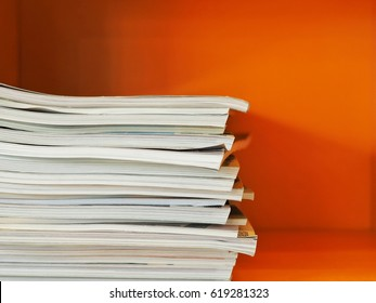 Stack of magazines with modern orange wall background.