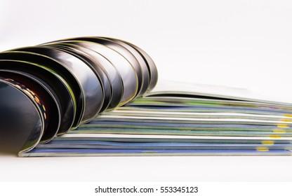 Stack of magazines on white background.