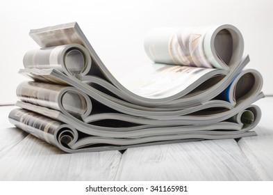 stack of magazines on a white-painted wooden table