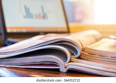 Stack of magazines with report on laptop, blur coffee shop background