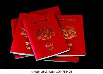 A stack of Malaysian passports isolated on a black background