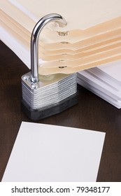 Stack of manila folders closed with a metal lock. Add your text to the white space.