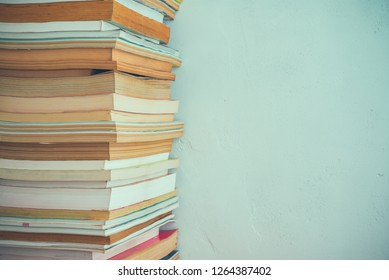 Stack of many old books on shelf in book store or library room with white wall background. Knowledge learning, education, bachelor degree in university or back to school concept.