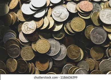 Stack of many old international coins. Background, texture. Concept economy crisis or numismatic collection. Dramatic toning. Close up.