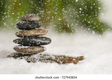 Stack of meditative rocks in the snow fall
