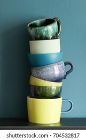 Stack of mismatched crockery in shades of blue, green and yellow