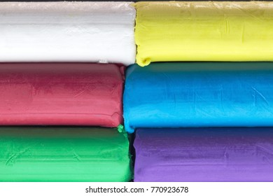 A stack of modeling clay with various colourful colors in white, yellow, red, blue, green and  purple
