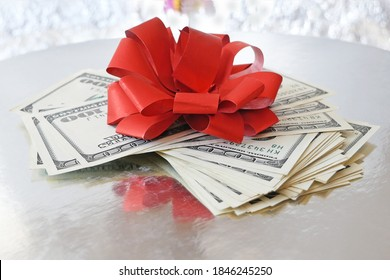 Stack of Money with Bow on silver xmas background, merry christmas, happy new year, wealth and health concept, closeup