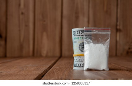 Stack of Money, drugsand on a wooden table. Drug use, crime, addiction and substance abuse concept on wooden background.