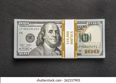 Stack of money wrapped in currency strap - $ 100 one hundred-dollar bills on black background. Top view