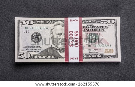 ede76fbfced7 Stack of money wrapped in currency strap -   50 fifty-dollar bills on black
