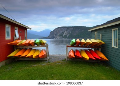 Stack of multicolored kayaks on the shore in beautiful landscape