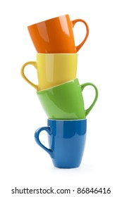 Stack of multicolored mugs isolated on a white background.