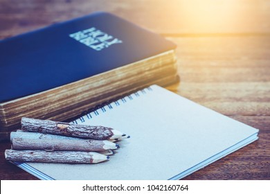 stack of natural hand made pencils on small note book and the holy bible on wooden background