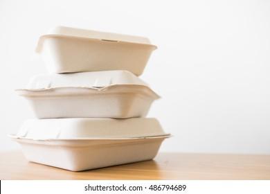 Stack of natural plant fiber food box on wooden background.
