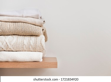 A stack of neatly folded warm knitwear, wool on a wooden shelf and a beige background. Capsule wardrobe, clothes storage, minimalism, knitted texture, order, comfort. Banner with copy space for text.
