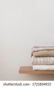 A stack of neatly folded warm knitwear, wool on a wooden shelf and a beige background. Capsule wardrobe, clothes storage, minimalism, knitted texture, order, comfort. Vertical, copy space.