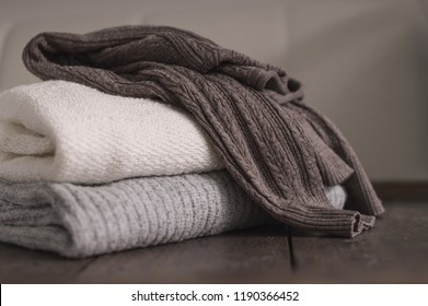 Stack of neatly folded woolen knitwear. Minimal lifestyle, capsule wardrobe. Autumn-winter men fashion wardrobe concept. Earth tones, horizontal copy space