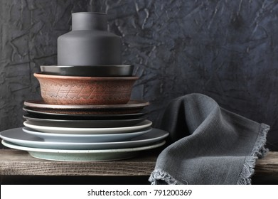 Stack of neutral colored dishware and linen napkin on distressed wooden shelf against rough plaster black wall. Kitchen utensils.