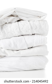 A stack of new clean white clothes of different fabrics on a white background, isolated