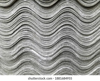 Stack of new corrugated slate sheets. Many gray slate sheets are stacked on top of each other. Wavy stripes pattern. Side view of the ends. Close-up. Selective focus. Copy space.