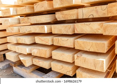 Stack of new wooden studs at the lumber yard. Timber on the construction site to dry. Background of sawed and processed wood of coniferous breeds