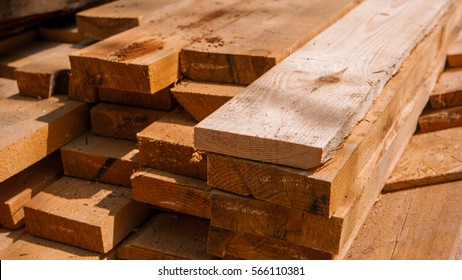 Stack of new wooden studs at a lumber yard, warm color retro tone selective focus image.