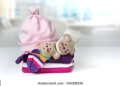 Stack of newborn baby girl clothes on white table indoors. Infant apparel accessories linen light background empty space for text.