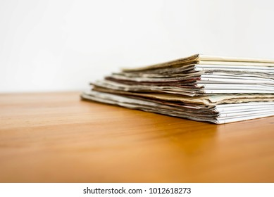 Stack of newspaper isolated on wood table