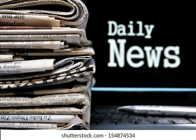 Stack of newspapers beside the lettering Daily News