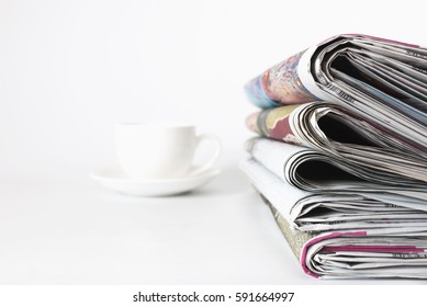 Stack of newspapers with coffee cup  isolated on white background.