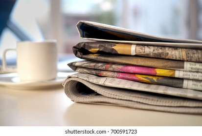 Stack of newspapers with computer an coffee cup