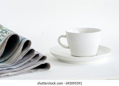 Stack of newspapers with cup of coffee isolated on white background.