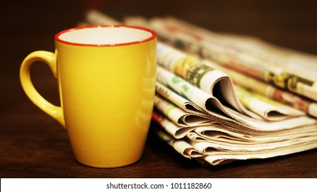 Stack of newspapers and cup of tea. Concept for English morning, reading fresh daily papers with news and having a breakfast. Journals and ceramic mug on wooden table, selective focus on pages