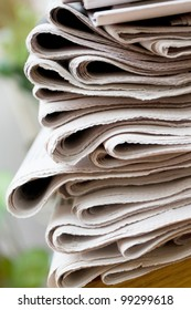 A stack of newspapers with focus on front
