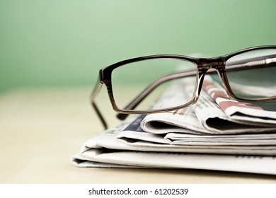 Stack of newspapers and glasses lying on table desaturated